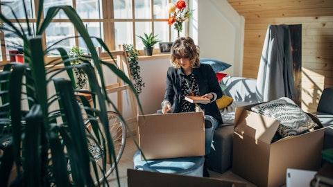 En kvinne sitter i leiligheten sin med pappesker rundt seg.