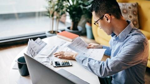 En mann studerer papirer med en kalkulator ved siden av seg.