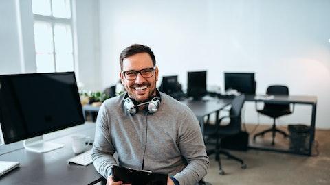 En mann sitter foran dataen og smiler bredt til kameraet.