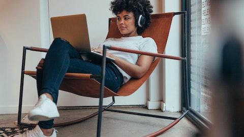 En kvinne sitter i en stol med hodetelefoner på hodet.