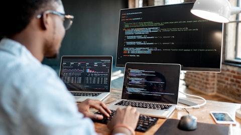 En mann sitter foran tre dataskjermer.