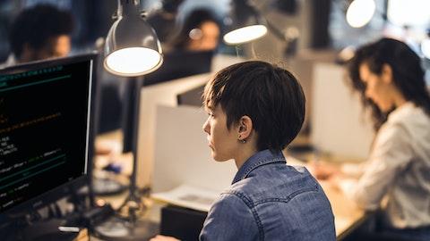 En kvinne sitter og jobber på dataen.