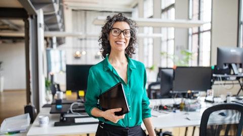 En kvinne står på kontoret og ser smilende mot kameraet.