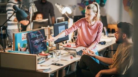 En kvinne forklarer noe på en dataskjerm for en mannlig kollega.