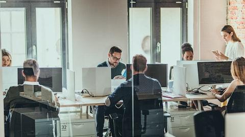 En rekke forretningspersoner sitter rundt et bord og jobber på laptopene sine.