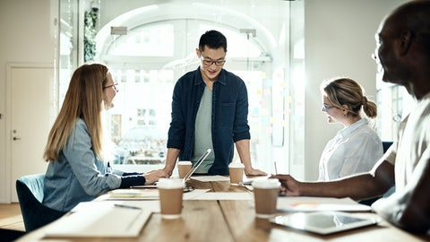 En mann står og lener seg ved et bord hvor det sitter tre andre personer.