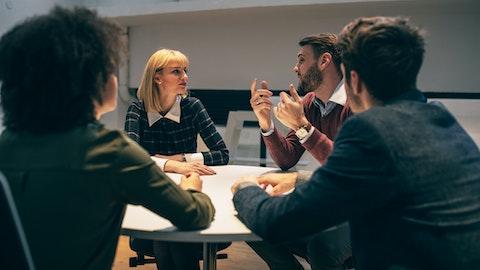 Fire personer sitter rundt et bord og diskuterer.