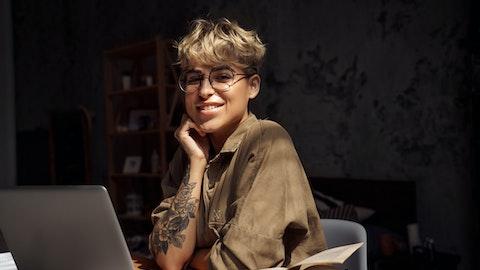 En kvinne med tatoveringer sitter foran laptopen.