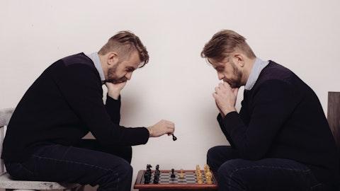 To menn som ser veldig like ut sitter og spiller sjakk.