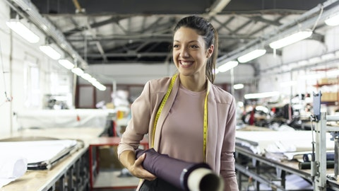 En kvinne står i en stoff-forretning med en stoffrull under armen.