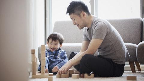 Far og sønn som leker med klosser på gulvet.