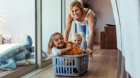 Mor med to barn som leker med en kleskurv.