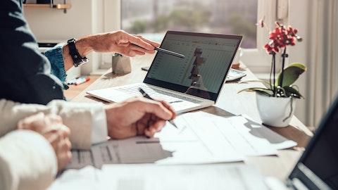 Et bord med laptop og flere papirer på.