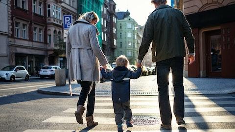 Et lite barn holder mor og far i hånden på vei over gangfeltet.
