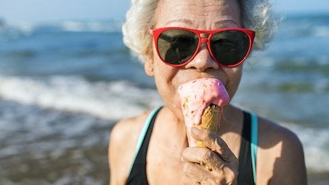 En eldre dame spiser iskrem på stranden.