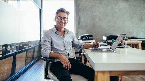 Mann som smiler og sitter ved en skrivepult.
