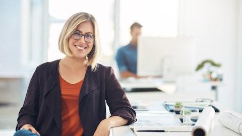 En glad kvinne med briller og lyst hår.