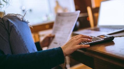 Kvinne som bruker kalkulator og PC for å beregne egenkapital