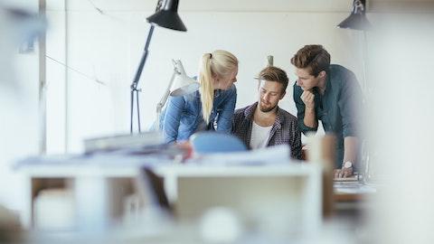 Tre unge voksne som samarbeider om en oppgave