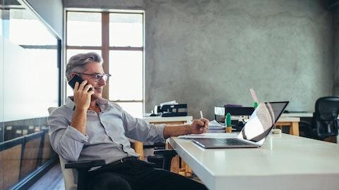 Mann i skjorte som snakker i telefonen foran sin laptop.