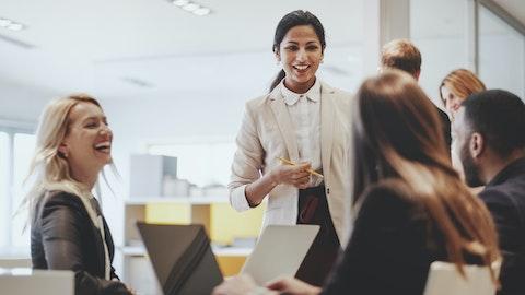 Glade mennesker i et møterom på arbeid.