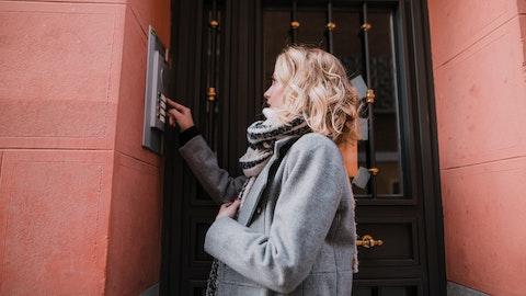 Kvinne som ringer på en dør.