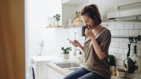 Kvinne som leser på mobilen mens hun sitter på kjøkkenbenken.