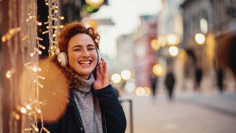 Kvinne står å lytter til podkast