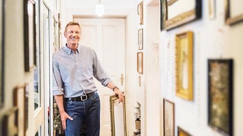 Glad mann i en lys hall med fotografier.