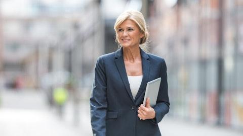 Smilende kvinne med lyst hår i blå dressjakke og bukse.