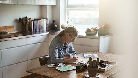 Kvinne som skriver ved en skrivepult.