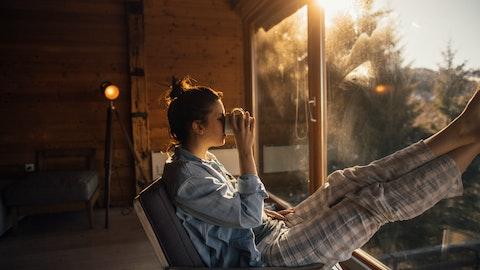 Dame i pysjamas som drikker kakao og ser ut av vinduet.