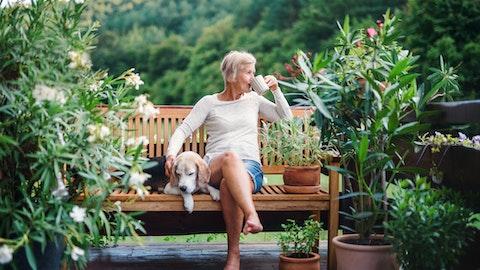 Eldre dame nyter en kaffe i parken med hunden sin.