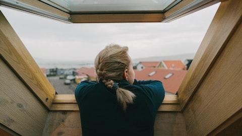 Nyinnflyttet ung jente nyter utsikten fra takvinduet.