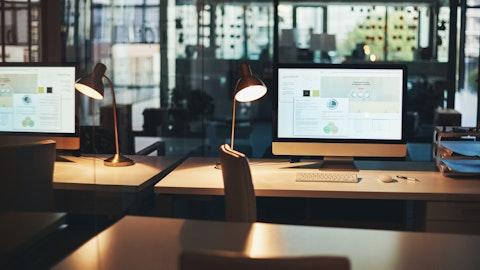 En skrivepult med en PC-skjerm som viser ulike kontrakter.