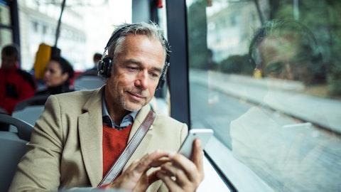 Mann sitter på bussen med hodetelefoner og mobil.