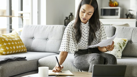 Ung kvinne arbeider foran laptopen med noen dokumenter.