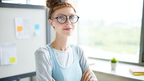 Rødhåret jente med briller står med armene i kryss og ser inn i kameraet.