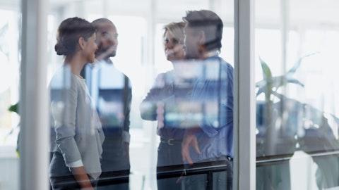 Fire mennesker som diskuterer bak en glassvegg.