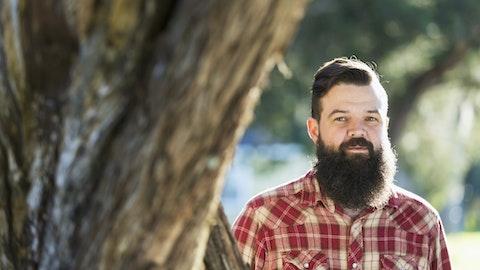 Mann som står ved et tre og ser inn i kameraet.