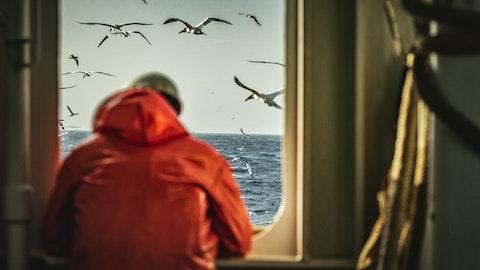 mann i rød regnfrakk ser ut over havet fra vinduet av et skip