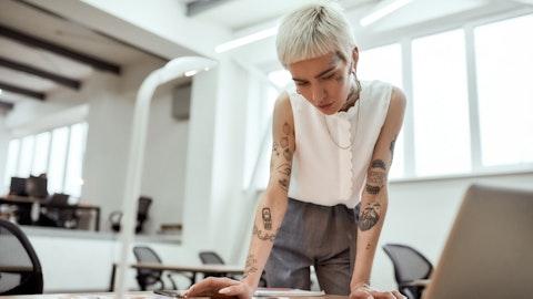 Kvinne med tatoveringer ser på noen dokumenter.