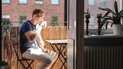En mann sitter på terrassen og drikker kaffe.