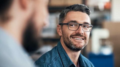Smilende mann med mørkt hår og briller.