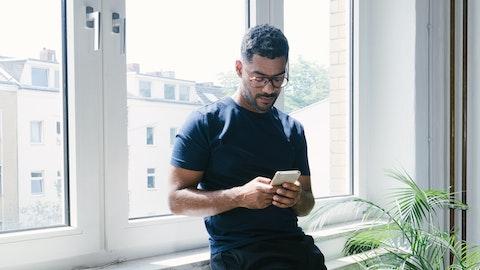 Ung mann som får oppsigelse tilsendt på mobilen.
