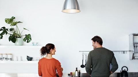 Et par som ser på hverandre mens de lager mat på kjøkkenet.
