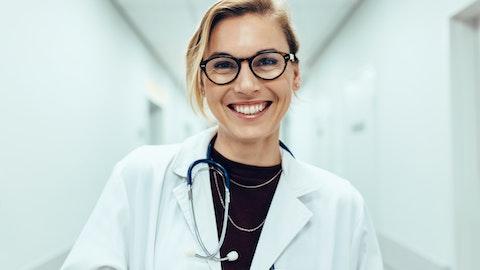 En kvinnelig glad lege som ser inn i kameraet.
