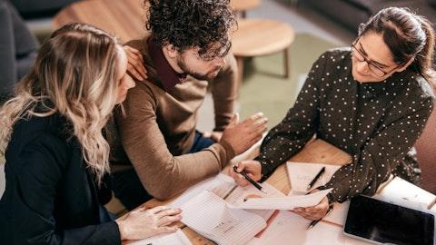 Arbeidsgiver snakker med to ansatte rundt et bord.