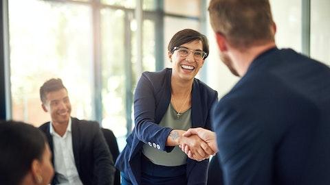 Kvinnelig advokat som smiler og håndhilser på en klient.