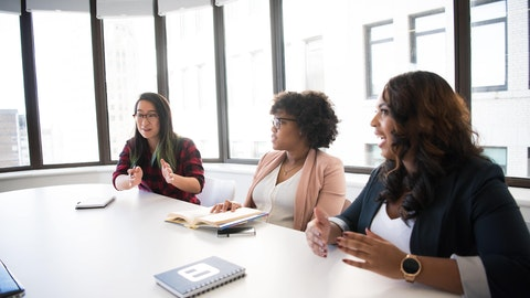 En gruppe mennesker som diskuterer i et grupperom.